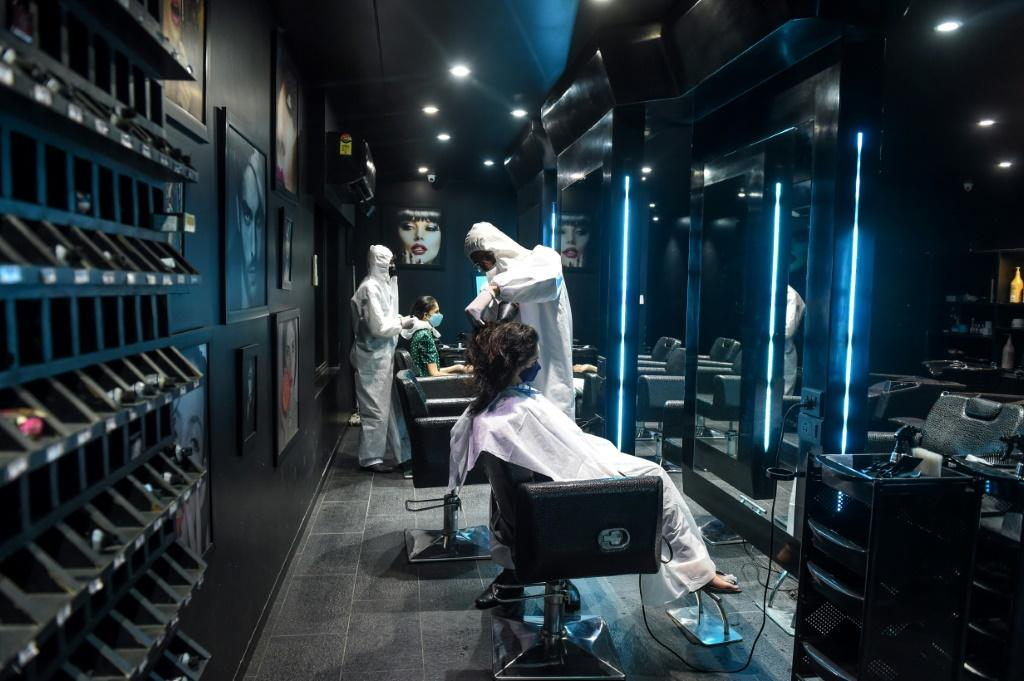 Hairdressers in protective suits attend to customers at a hair and beauty salon in Ahmedabad, India