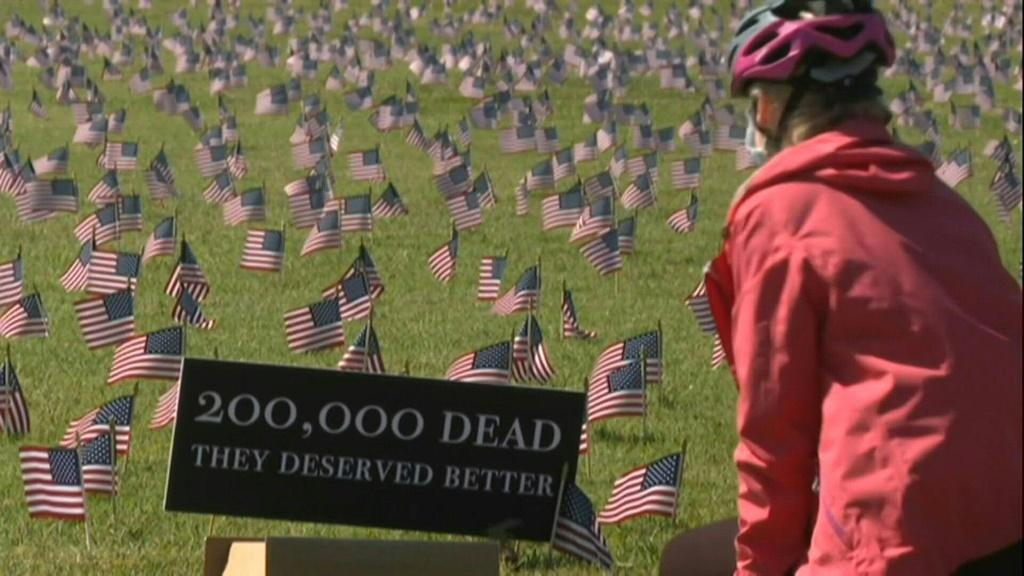 Volunteers from the COVID Memorial Project have placed 200,000 American flags on the National Mall as the United States crosses the threshold of 200,000 lives lost in the COVID-19 pandemic.
