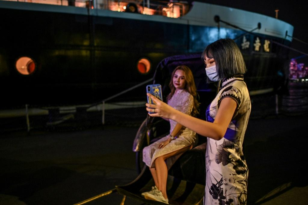 Party-goers in traditional 1920s outfits take pictures before embarking on a theme cruise in Wuhan