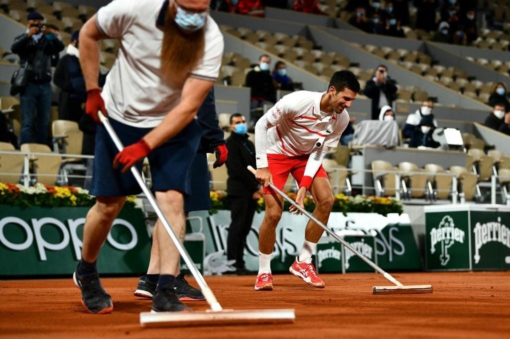 Sweeping to victory: Novak Djokovic helps groundstaff lay more clay to dry the surface after rain fell on Court Philippe Chatrier