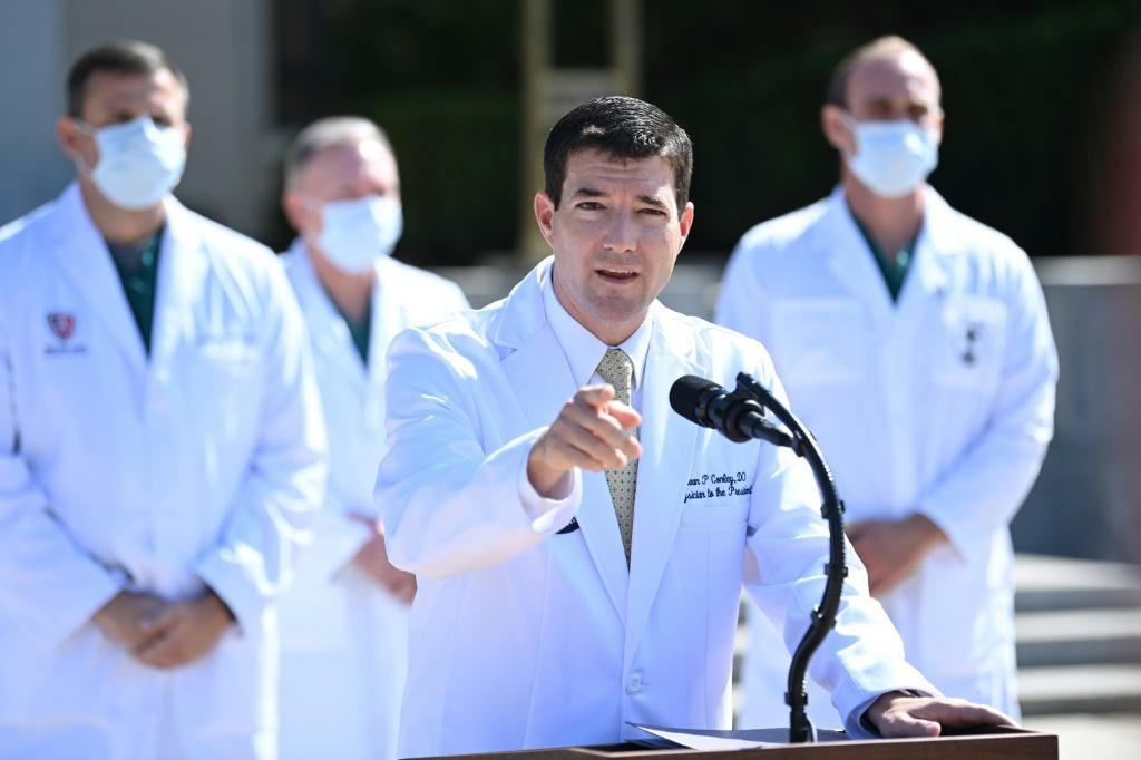 White House physician Sean Conley answers questions surrounded by other doctors, during an update on the condition of US President Donald Trump, on October 4, 2020, at Walter Reed Medical Center in Bethesda, Maryland