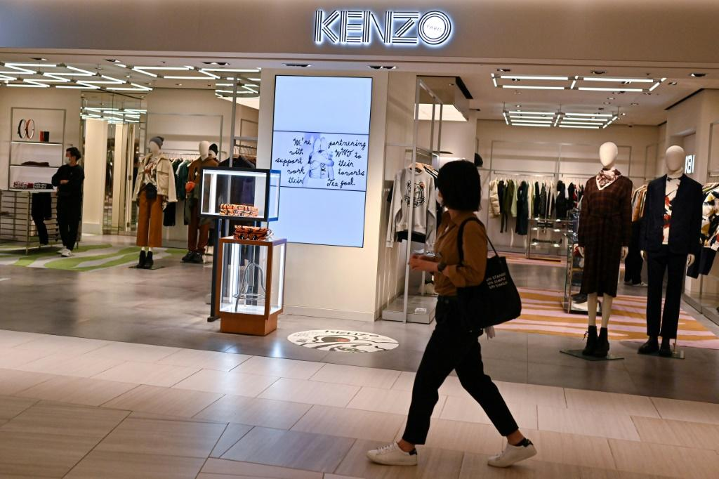 A woman walks past a Kenzo outlet in Tokyo a day after the death of founder Kenzo Takada in Paris aged 81