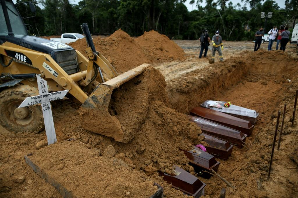 An excavator pushes earth over coffins at a mass grave at the Nossa Senhora cemetary in Manaus, Amazon state, Brazil in September 2020