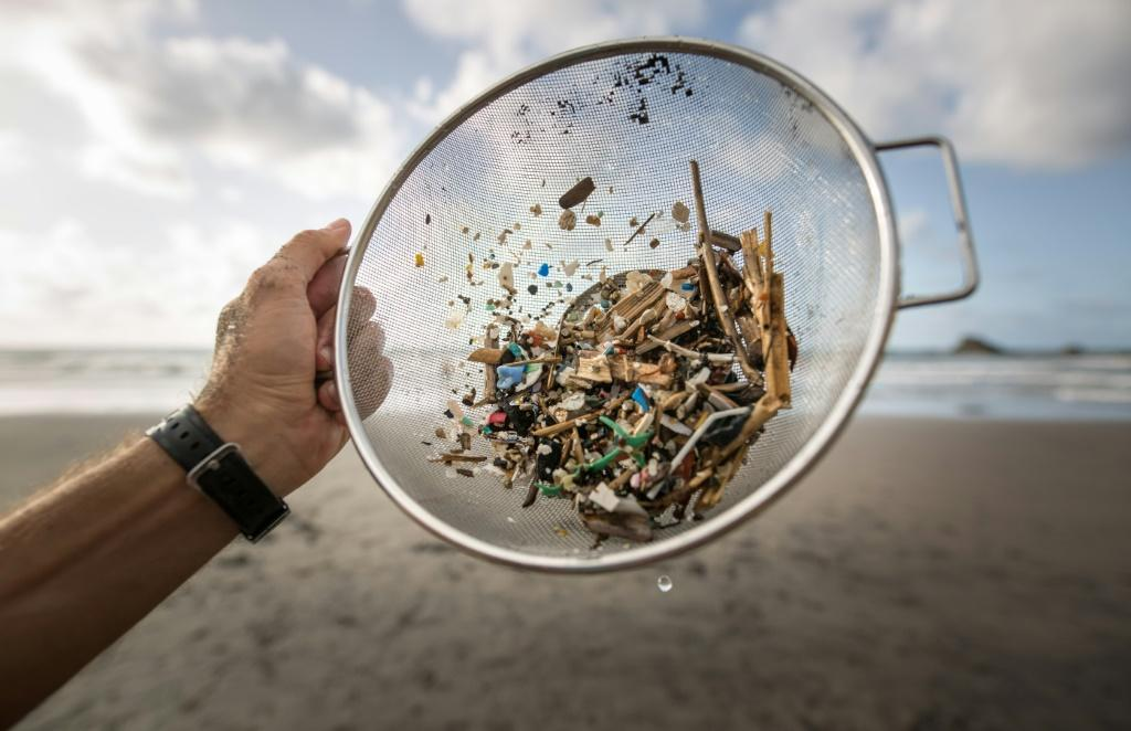 A volunteer of the NGO 'Canarias Libre de Plasticos' (Canary Islands free of plastics) carries out a collection of microplastics and mesoplastic debris to clean the Almaciga Beach, on the north coast of the Canary Island of Tenerife, on July 14, 2018.