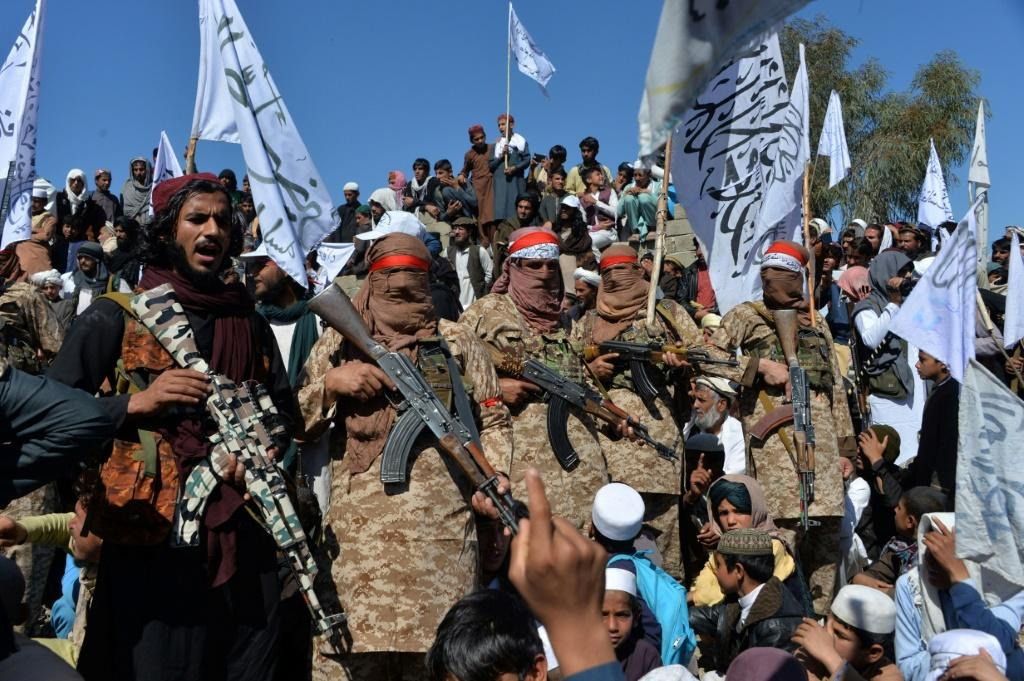 Afghan Taliban militants and villagers in Laghman province celebrate on March 2, 2020 after the peace deal with the United States
