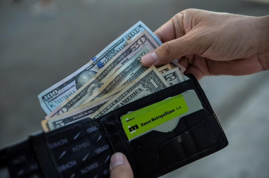 A man shows his wallet with US dollars on a street in Havana, Cuba, in September 2020