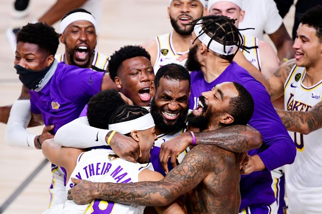 LeBron James celebrates with Los Angeles teammate Quinn Cook and others after the Lakers' championship-clinching 106-93 victory over the Miami Heat in game six of the NBA Finals