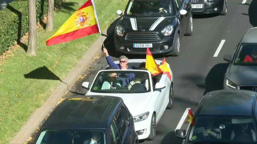 Protesters called out by the far-right party Vox drive through Madrid to protest the state of emergency the government imposed to fight a resurgence in the coronavirus
