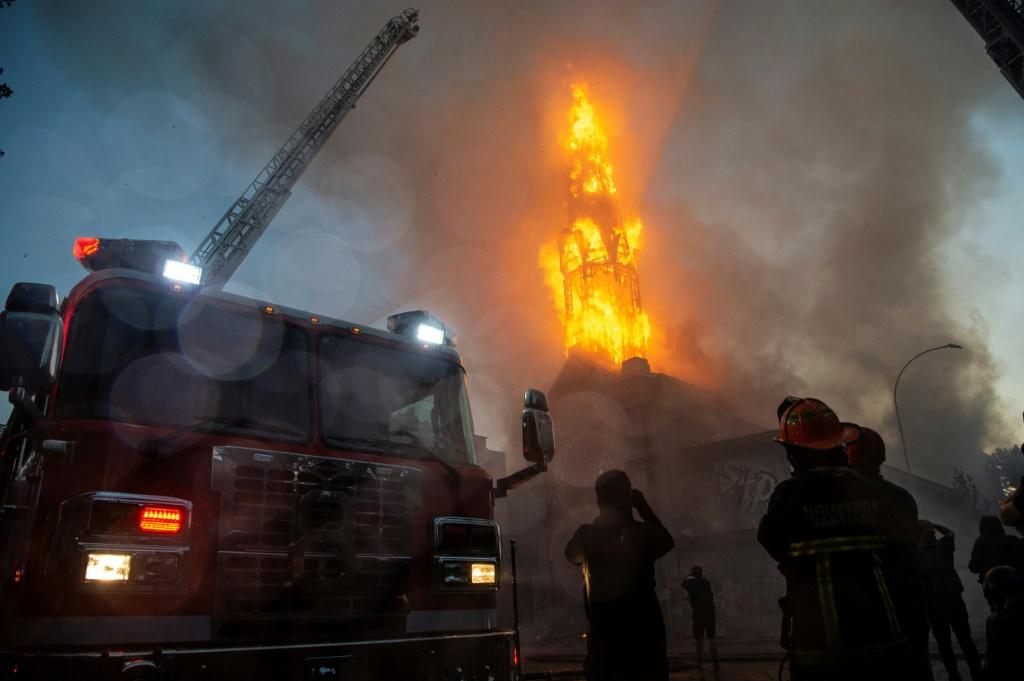Firefighters work outside the burning church of Asuncion after it was set on fire by demonstrators in Santiago