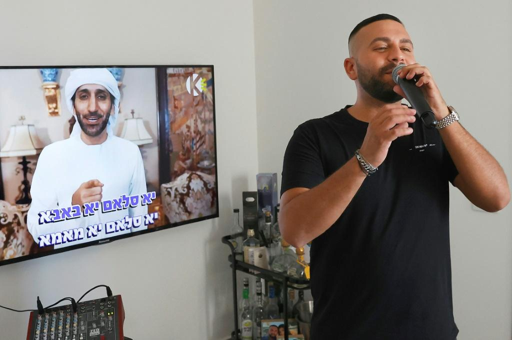 Israeli singer Elkana Marziano, 28, sings along with a video clip of his collaboration with Emirati artist Walid Aljasim (image on screen)