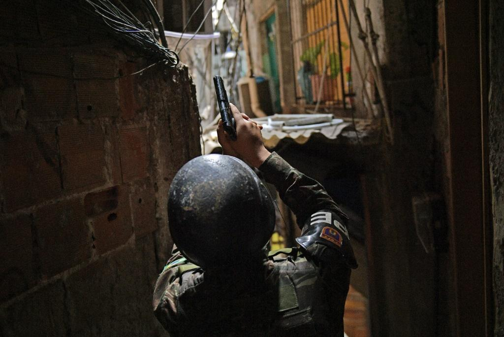 A militarized police officer holds his gun in an alley way at Rocinha favela in Rio de Janeiro, Brazil, on September 25, 2017