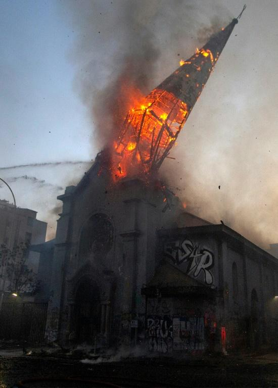The spire of the Church of the Assumption collapses after severe fire damage