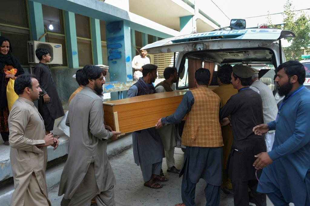 Relatives carry the coffin of a victim, who was killed in a stampede, outside a mortuary in Jalalabad on October 21, 2020