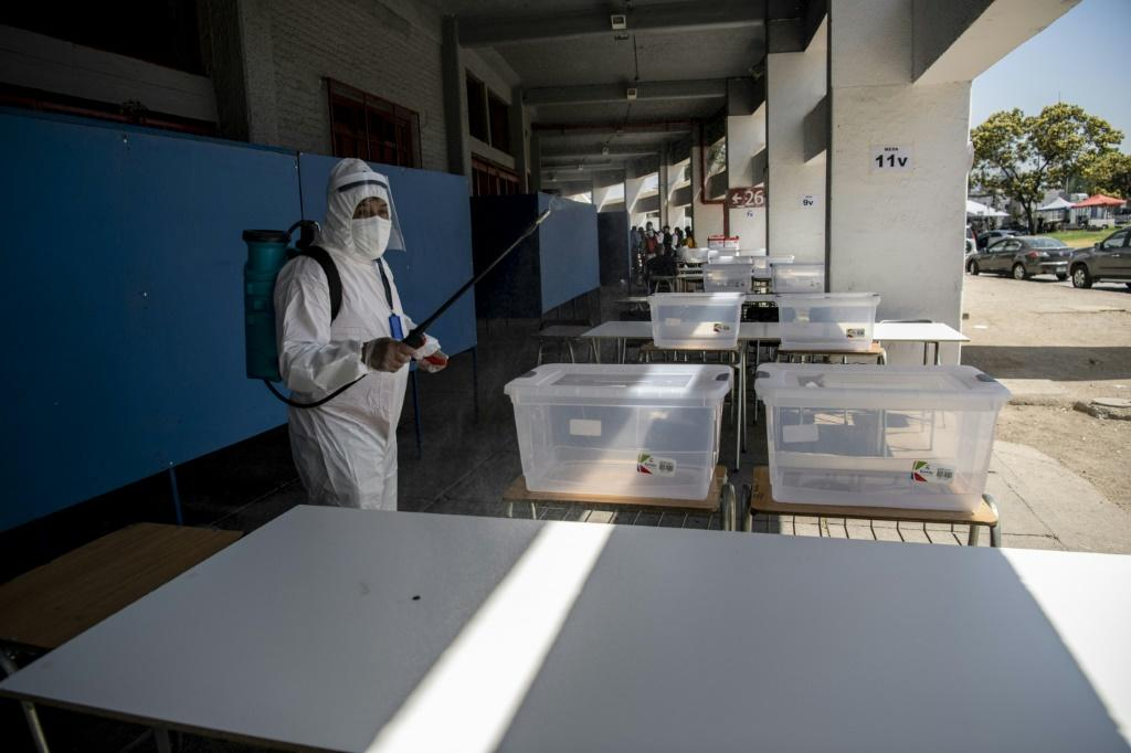 A worker disinfects a polling station in Santiago on the eve of Chile's constitutional referendum, which is being held as the country battles the coronavirus epidemic