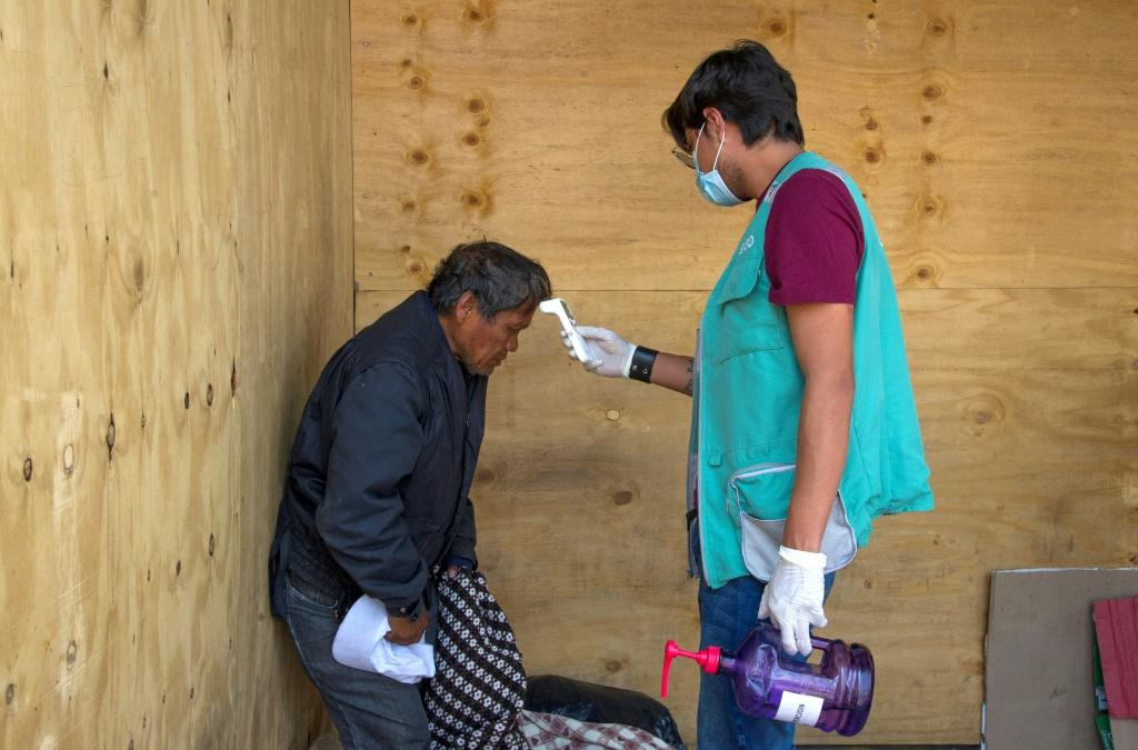 A health worker takes the temperature of a homeless man in Mexico City during the coronavirus pandemic