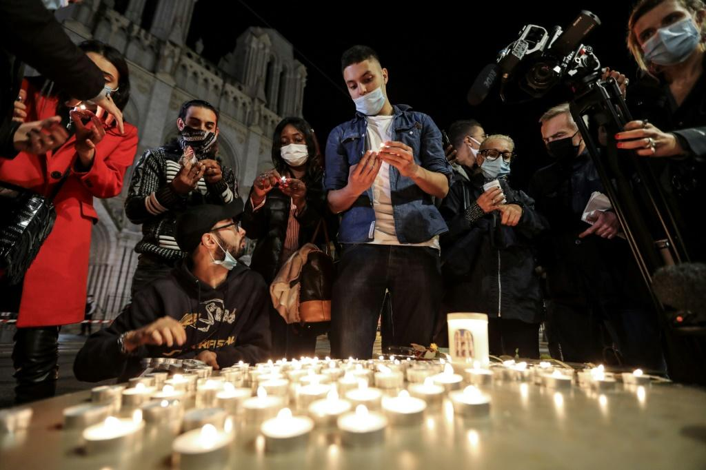 People lights candle outside the Notre-Dame de l'Assomption Basilica in Nice in tribute to the three victims of a knife rampage, which France's president called an 'Islamist terrorist attack'
