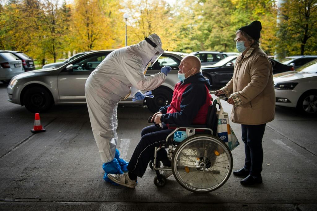A medic tests a man for the novel coronavirus during nationwide testing in Bratislava, Slovakia on October 31, 2020.