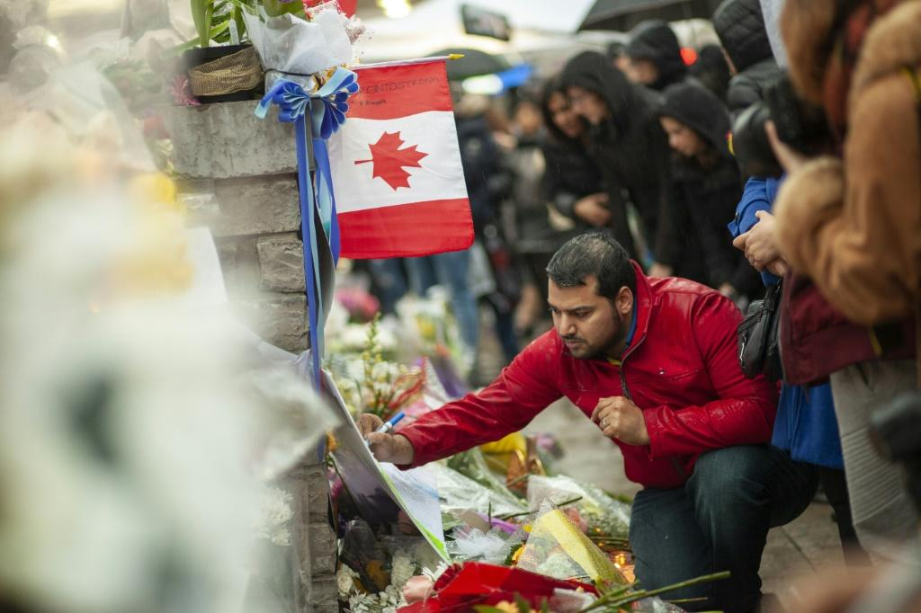 A man writes a message at a memorial near the site of the deadly van attack in April 2018 in Toronto