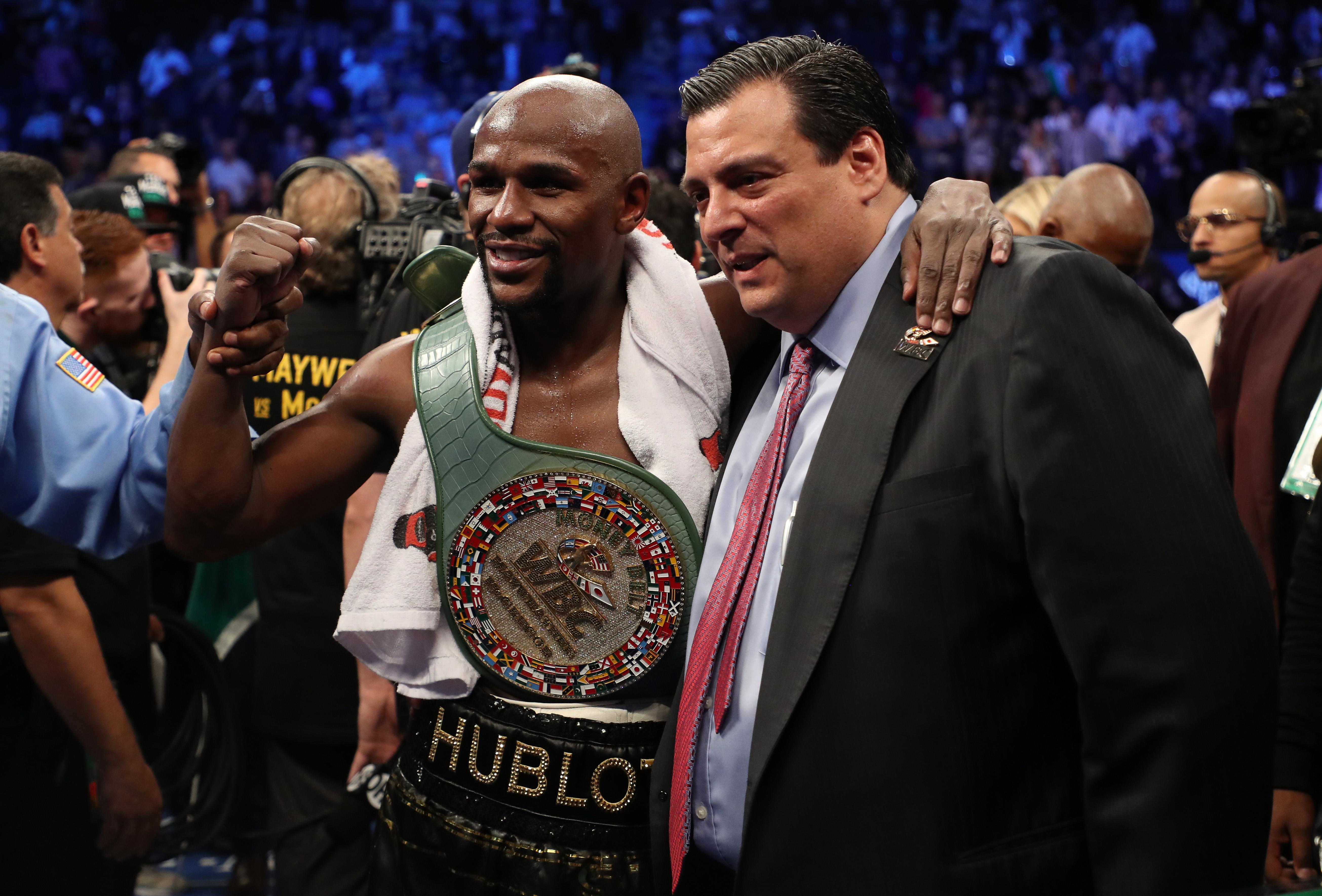 Floyd Mayweather Jr. celebrates with WBC President Mauricio Sulaiman and the WBC Money Belt after his TKO of Conor McGregor in their super welterweight boxing match
