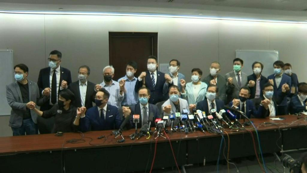 Hong Kong's pro-democracy lawmakers say they would resign after China gave the city the power to disqualify politicians deemed a threat to national security and four of their colleagues were ousted.