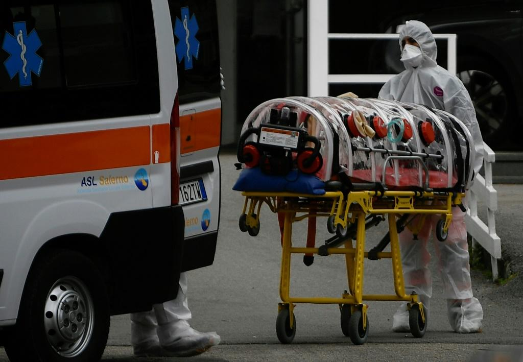 Medical workers arrive at a hospital in Naples in an ambulance with a COVID-19 patient