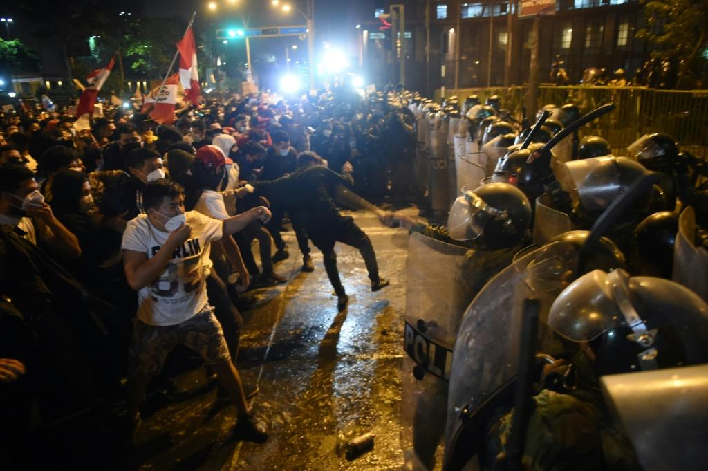 Demonstrators confront riot police during a protest in Lima against the ousting of popular president Martin Vizcarra by Congress