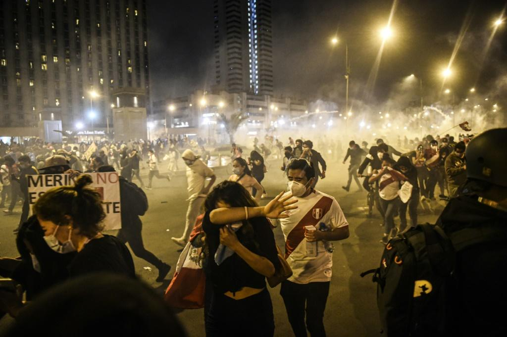 Demonstrators run away from tear gas during a protest in Lima
