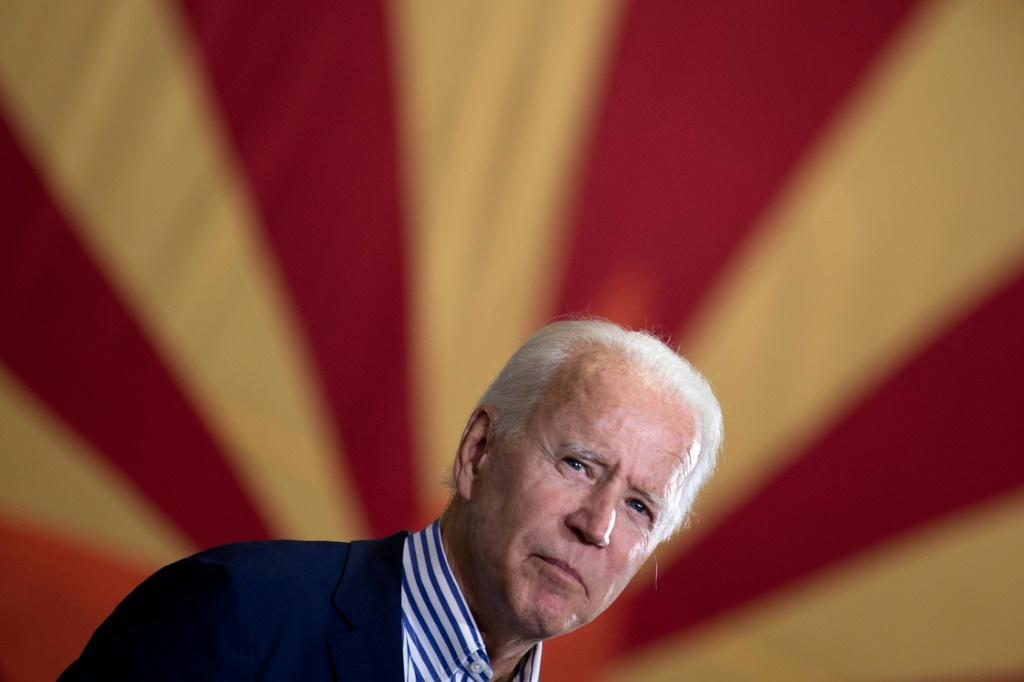 President-elect Joe Biden (pictured in front of Arizona's state flag) has flipped Arizona Democratic for the first time since Bill Clinton's win in 1996
