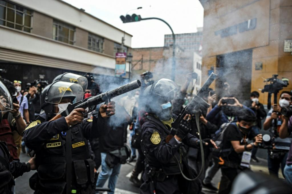 Riot police fire tear gas as they try to disperse supporters of ousted Peruvian president Martin Vizcarra in Lima, November 2020