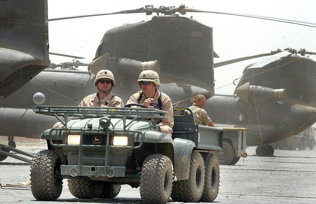 US soldiers drive past Chinook helicopters in 2002, a year after the invasion of Afghanistan at Bagram Air Base, which has become a center of US military power after nearly two decades of war