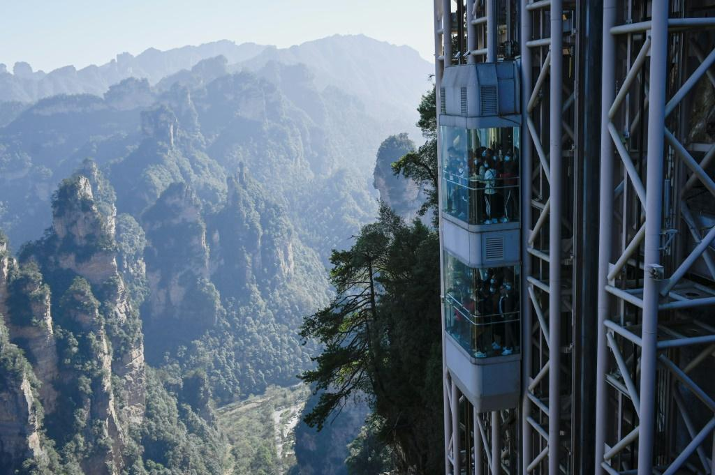 "Located in China's Zhangjiajie Forest Park, the world's highest outdoor lift carries tourists up the cliff face that inspired the landscape for the movie ""Avatar"