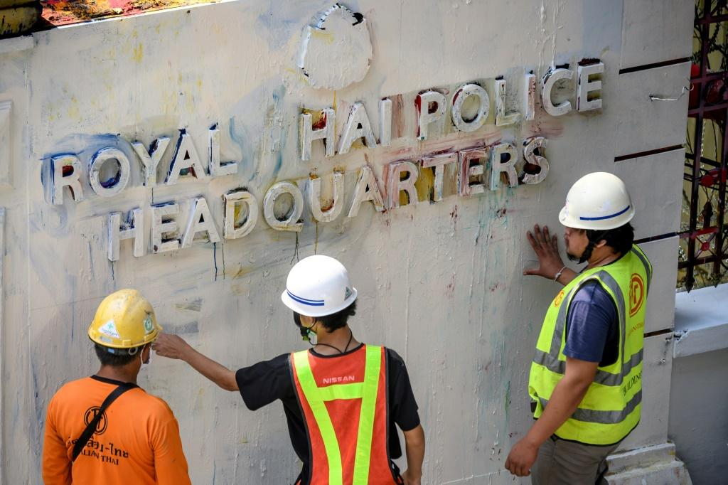 Workers clear up after protesters daubed graffiti on the walls of the Thai police headquarters
