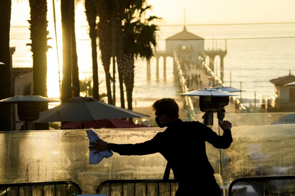 A restaurant employee cleans a plexiglass table divider while preparing for outdoor dining service in Manhattan Beach, California, a few hours before the start of the new 10:00 pm to 5:00 am curfew