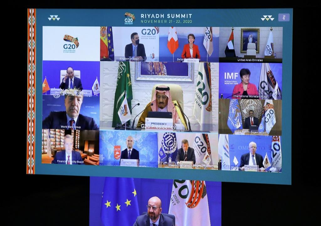 European Council President Charles Michel (down) and Saudi Arabia's King Salman bin Abdulaziz Al Saud are seen with other state and institution leaders on a screen before the start of a virtual G20 summit hosted by Saudi Arabia