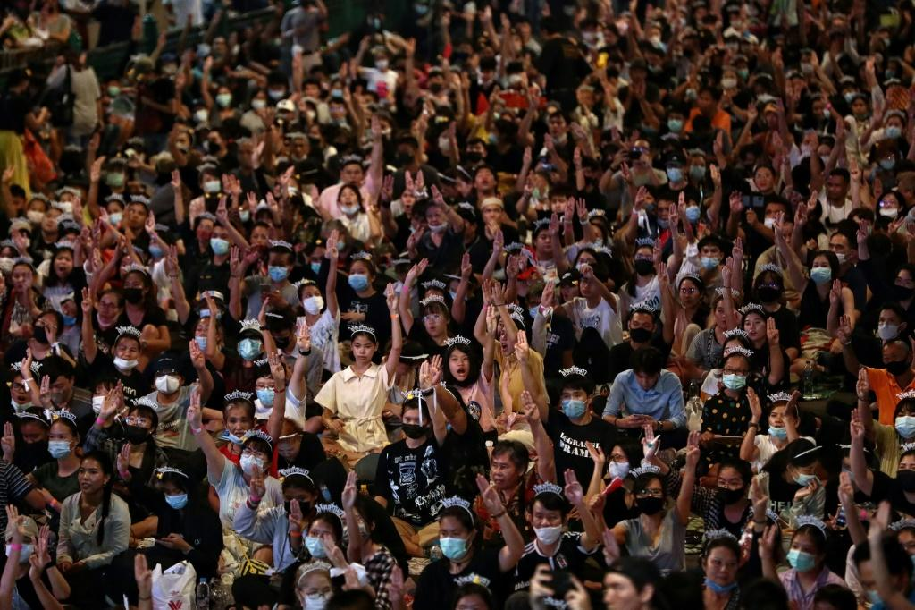 Pro-democracy protesters hold up the three-finger salute at a pro-democracy protest in Bangkok