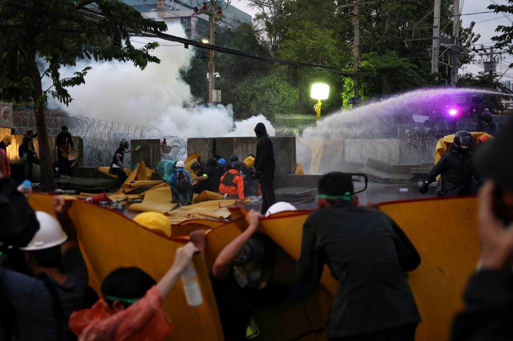 Pro-democracy protesters take shelter from police water cannons in Bangkok