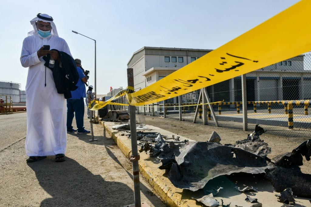 A man checks his phone while standing near debris following an attack at the Saudi Aramco oil facility in Saudi Arabia's Red Sea city of Jeddah on November 24, 2020