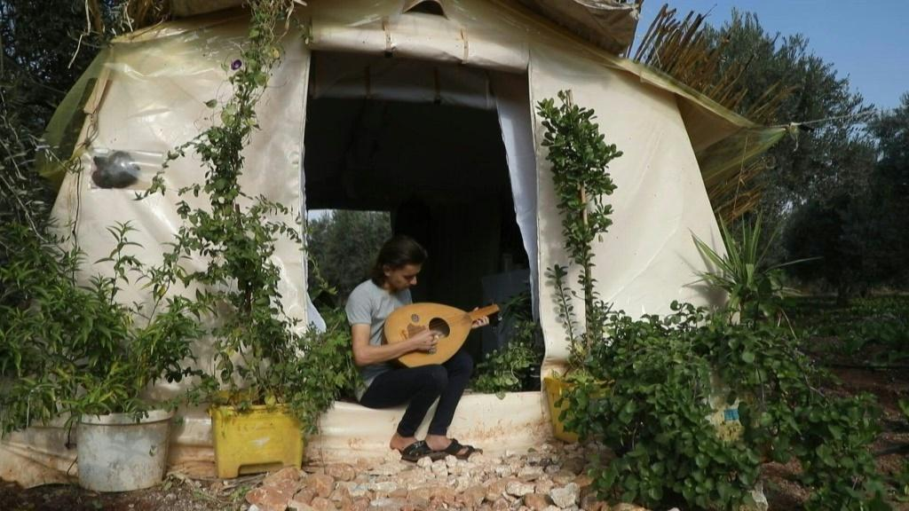 Among the olive trees in northwestern Syria, displaced teenager Wissam Diab plucks an oud outside his new home. Syria's war forced the Diab family to flee their village of Kafr Zita so 19-year-old Wissam decided to recreate his childhood home.