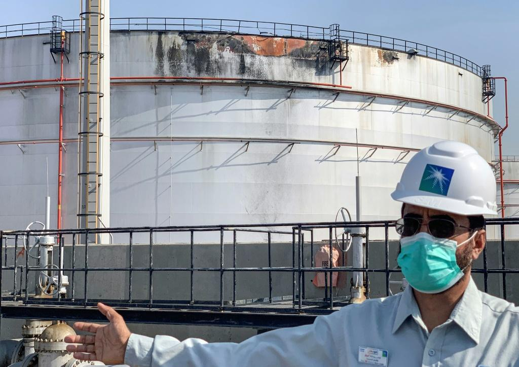 An employee at the Saudi Aramco oil facility in Jeddah on Tuesday stands near a tank that was damaged in a strike a day earlier