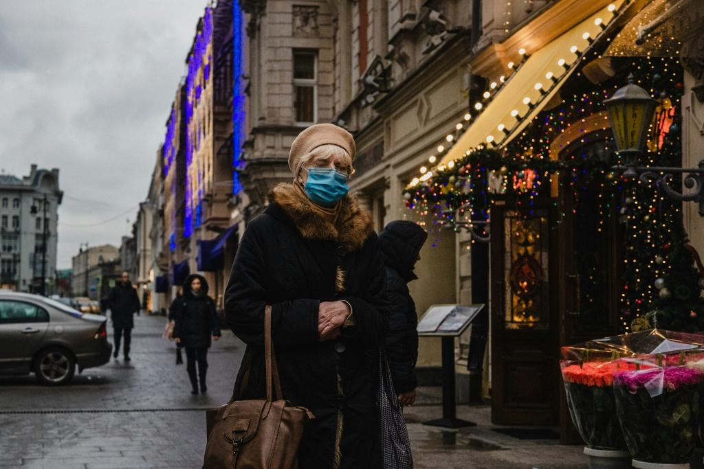 A woman wearing a face mask walks down a street in central Moscow on November 25, 2020, as cases continue to climb globally