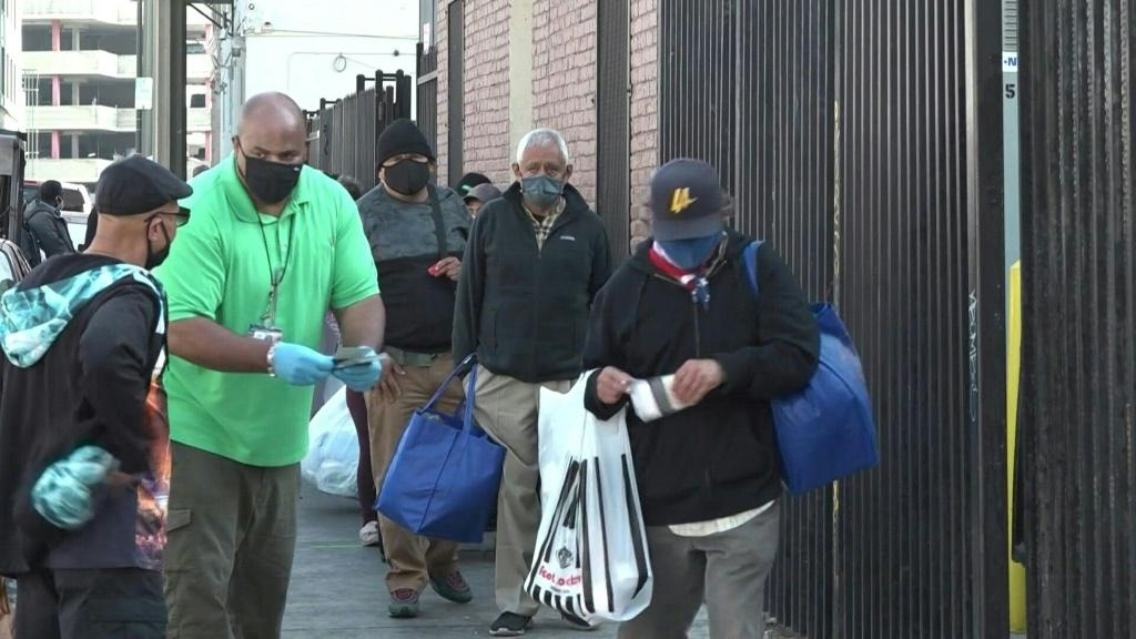 """IMAGES AND SOUNDBITESDespite the Covid-19 pandemic, the Los Angeles Mission maintains it's annual food distribution to help nourish those struggling to make ends meet this Thanksgiving. """"A hot meal, it warms your heart,"""" says one beneficary."""