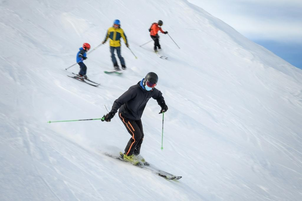 Skiers wearing protective face masks against the spread of the Covid-19 hit the slopes in the Swiss Alpine ski resort of Verbier on November 15, 2020