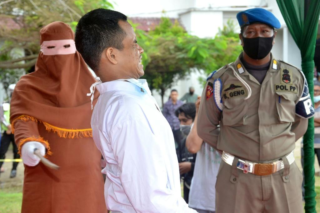 A man grimaces as he is flogged in Aceh, Indonesia, after being found guilty of raping a child