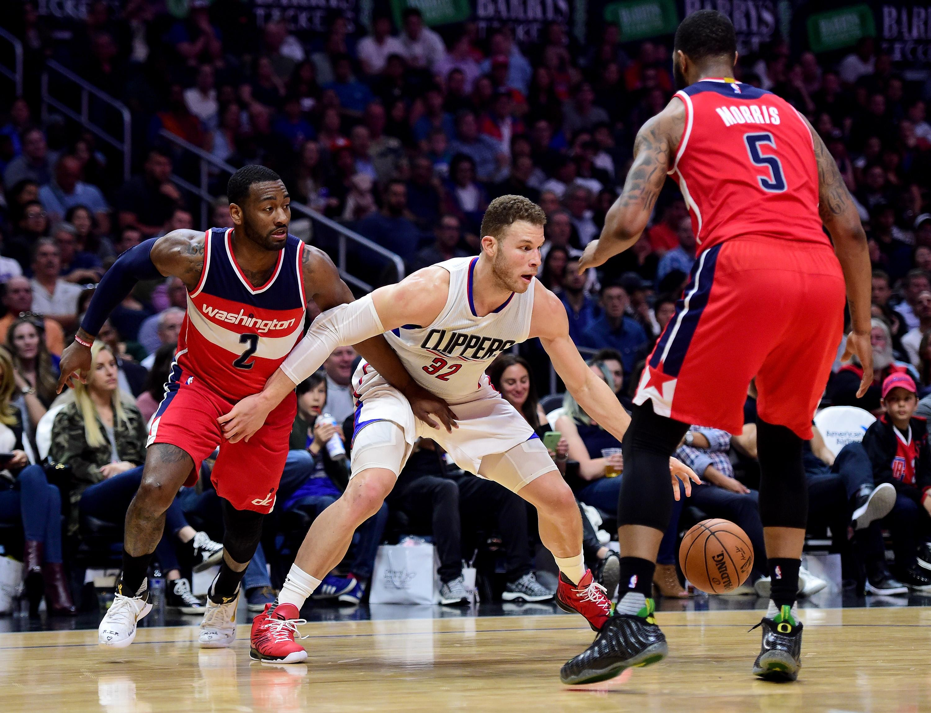 Blake Griffin #32 of the LA Clippers keeps his dribble from John Wall #2 and Markieff Morris #5 of the Washington Wizards