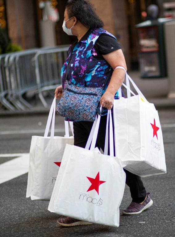 A shopper carries bags as she leaves Macy's department store in New York on Black Friday