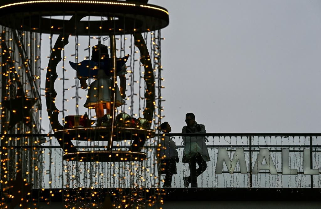 Customers stand on a balcony next to Christmas decorations in a shopping mall in Berlin. Germany plans to ease virus curbs for Christmas