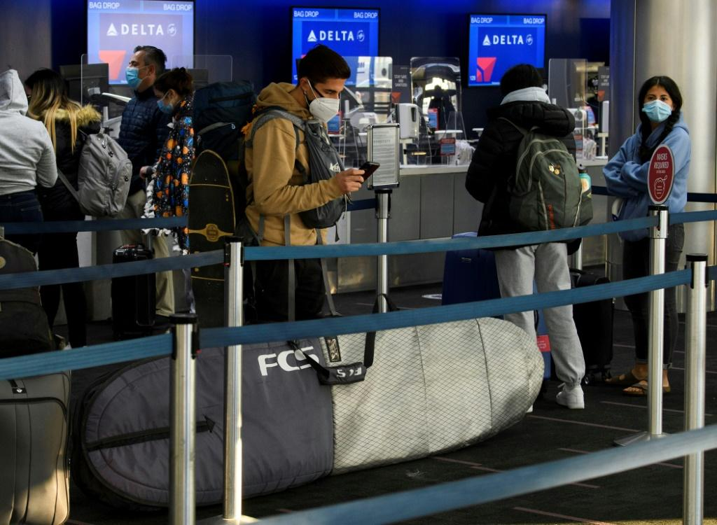 Passengers wait in line to check-in for Delta Air Lines flights at Los Angeles International Airport ahead of the Thanksgiving holiday in Los Angeles, California, on November 25, 2020