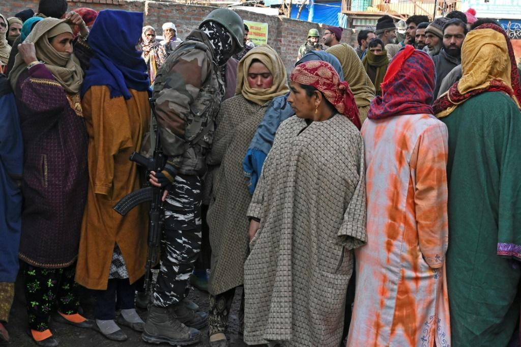 A paramilitary soldier walks next to voters queueing to cast their ballots at a polling station in Indian-administered Kashmir