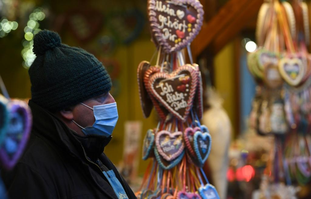 An employee wears a protective mask at a sales booth at the drive-in Christmas market in Landshut