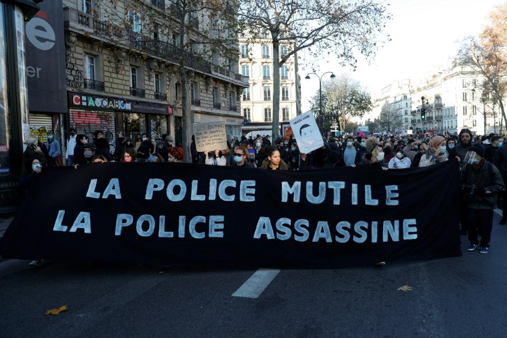 Demonstrators hold a sign reading 'Police mutilate police kill' on the Place de la Republique in Paris